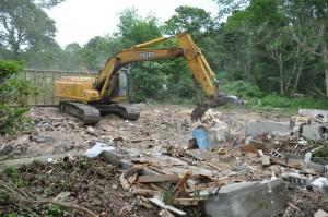 Bulldozer tearing down house